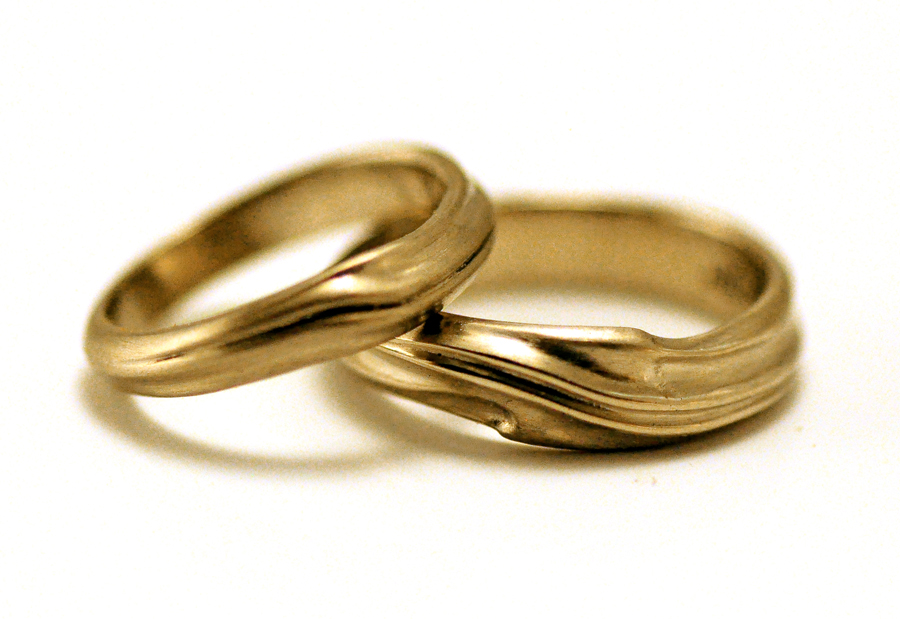 """Men's and women's wedding bands and free-flowing """"Genesis"""" style in 14 and 18 karat gold"""